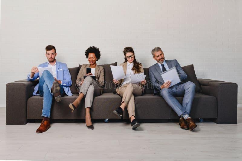 Verschiedene Geschäftsleute, die auf eine Verabredung warten stockfotos