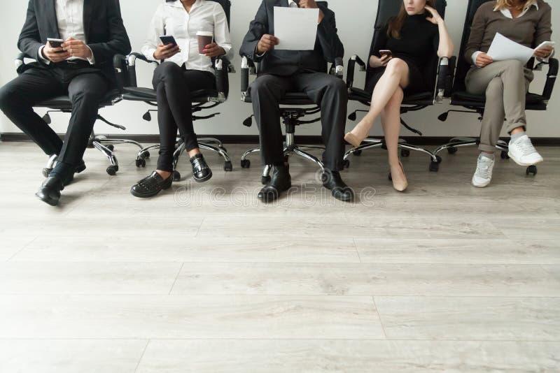 Verschiedene Geschäftsleute, die in die Reihe hält Smartphones warten und stockfotos