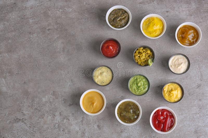 Verschiedene geschmackvolle Soßen in den Schüsseln auf grauer Tabelle stockfotografie