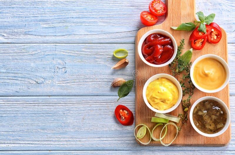 Verschiedene geschmackvolle Soßen in den Schüsseln auf hellem Holztisch lizenzfreies stockfoto