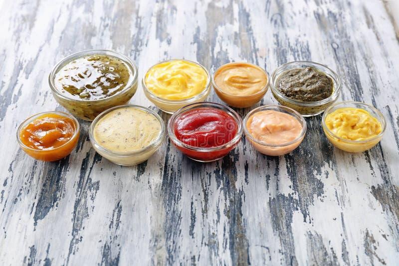 Verschiedene geschmackvolle Soßen in den Schüsseln auf Holztisch lizenzfreie stockfotos