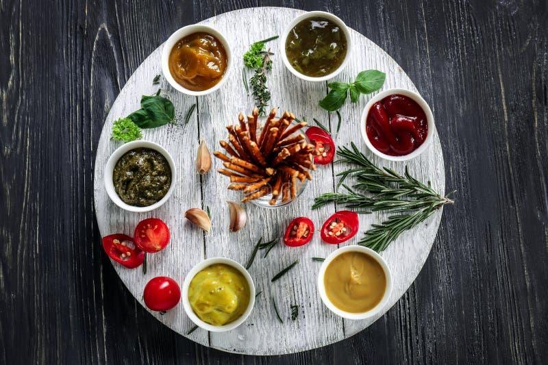 Verschiedene geschmackvolle Soßen in den Schüsseln auf Holztisch lizenzfreies stockfoto