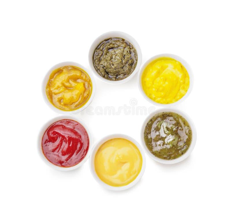 Verschiedene geschmackvolle Soßen in den Schüsseln auf weißem Hintergrund stockfoto