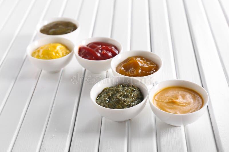 Verschiedene geschmackvolle Soßen in den Schüsseln auf weißem Holztisch stockfotos