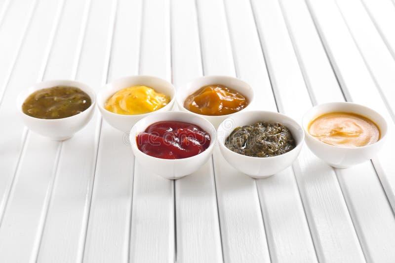 Verschiedene geschmackvolle Soßen in den Schüsseln auf weißem Holztisch lizenzfreies stockfoto
