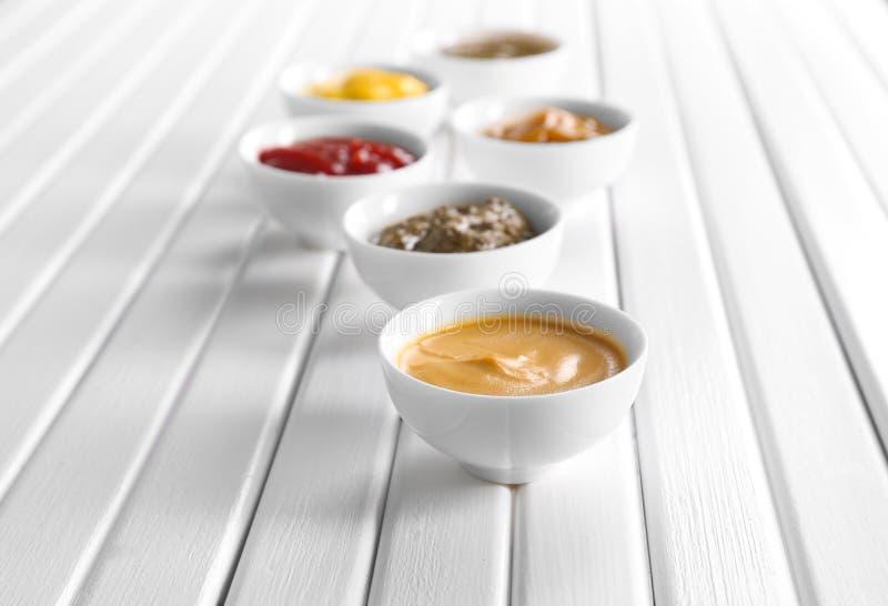 Verschiedene geschmackvolle Soßen in den Schüsseln auf weißem Holztisch stockbild