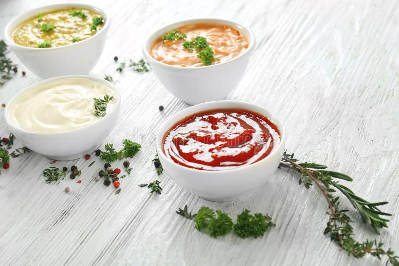 Verschiedene geschmackvolle Soßen in den Schüsseln mit Gewürzen auf weißem Holztisch stockfoto