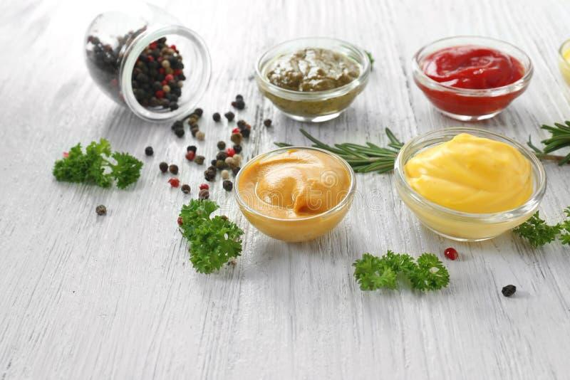 Verschiedene geschmackvolle Soßen in den Schüsseln mit Gewürzen auf weißem Holztisch lizenzfreie stockbilder