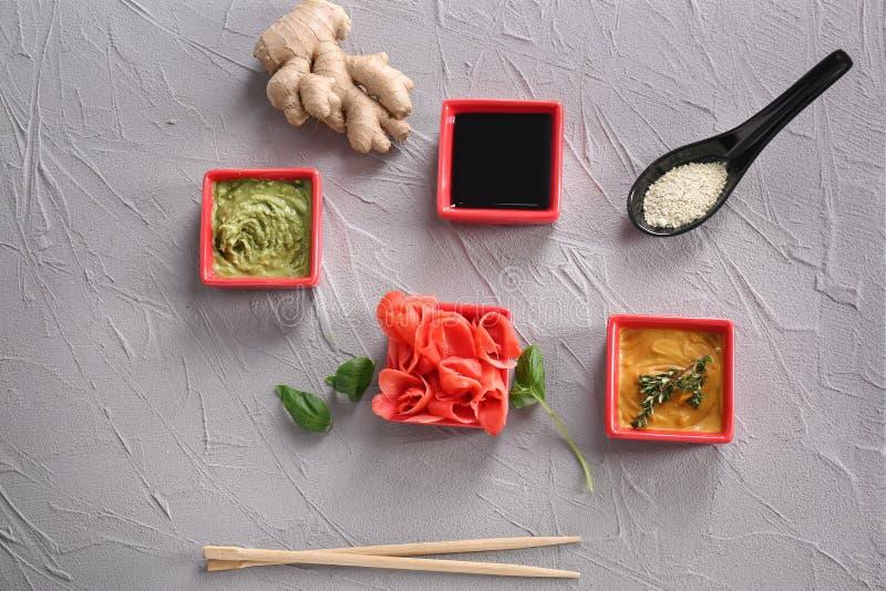 Verschiedene geschmackvolle Soßen mit mariniertem Ingwer in den Schüsseln auf grauem Hintergrund lizenzfreies stockbild