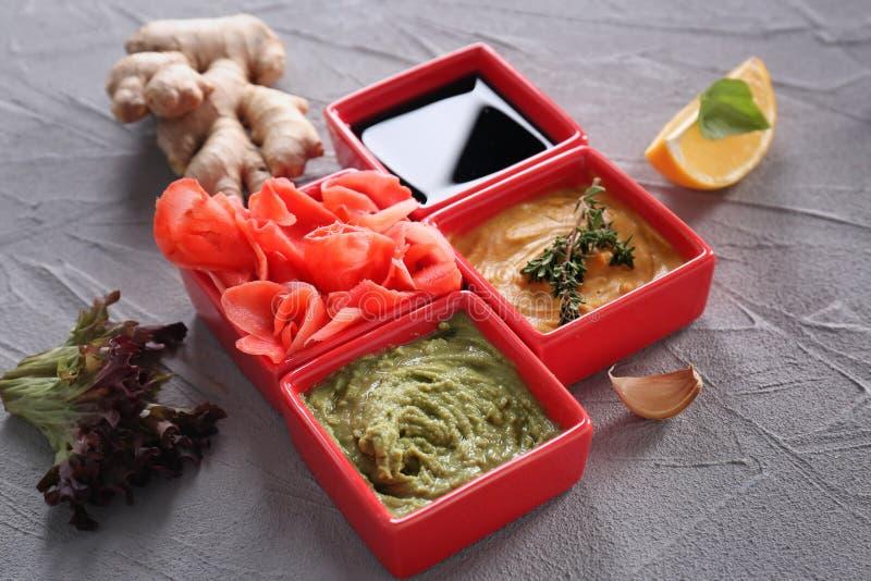 Verschiedene geschmackvolle Soßen mit mariniertem Ingwer in den Schüsseln auf grauem Hintergrund stockbild