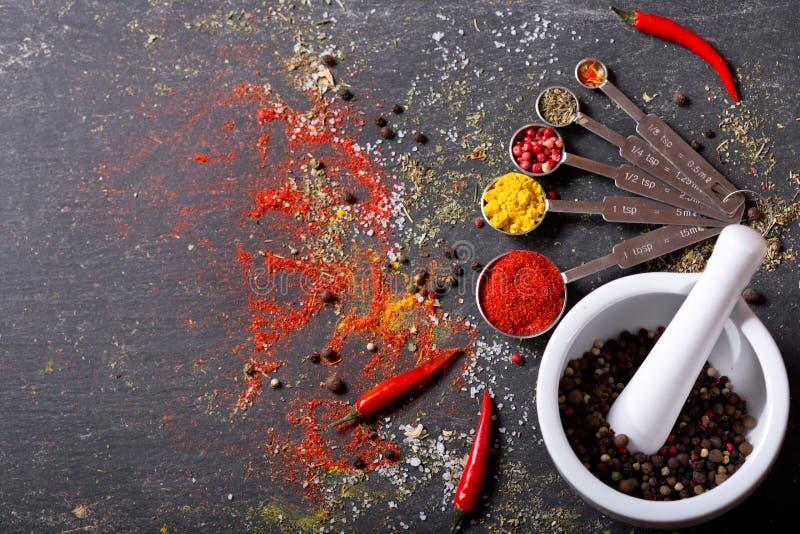 Verschiedene Gewürze für das Kochen auf dunkler Tabelle lizenzfreie stockfotos