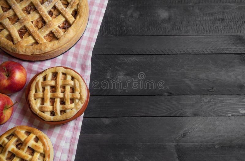 Verschiedene Größenapfelkuchen auf einer rustikalen Tabelle Über Ansicht mit Kopienraum stockbild