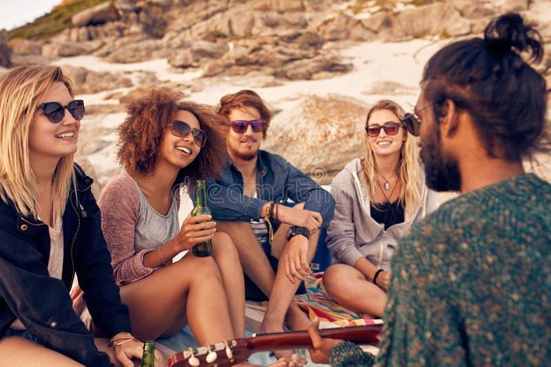 Verschiedene Gruppe Freunde, die heraus am Strand hängen stockbilder