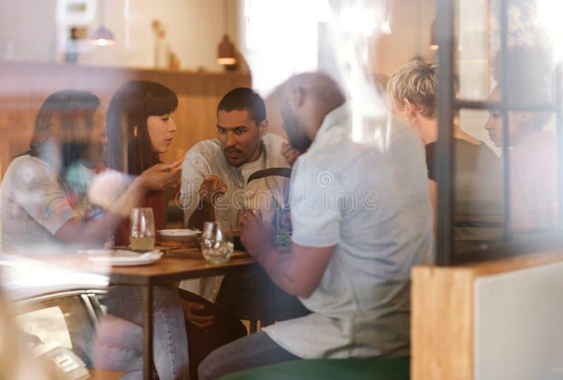 Verschiedene Gruppe junge Freunde, die zusammen in einer Bistro essen stockbild