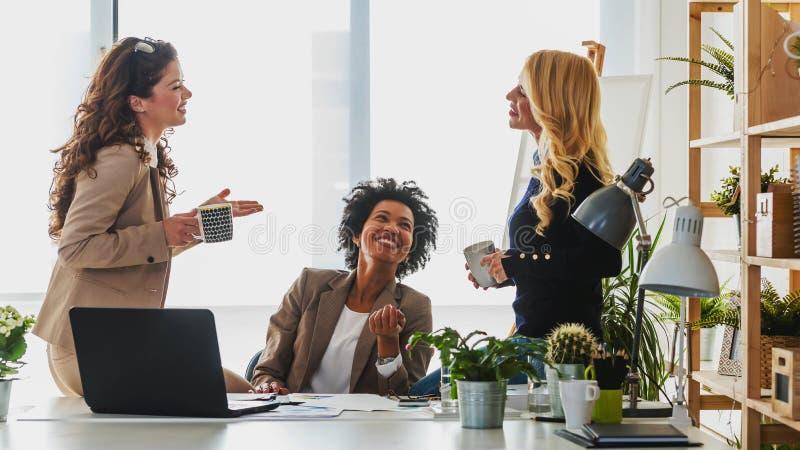 Verschiedene Gruppe lächelnde Geschäftsfrauen, die einen Bruch bei der Bürounterhaltung haben lizenzfreies stockbild