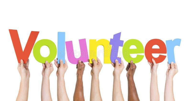 Verschiedene Hände, die den Wort-Freiwilligen halten lizenzfreie stockfotografie