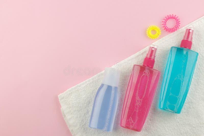 Verschiedene Haarpflegeprodukte und verschiedene Haarzusätze auf einem hellen rosa Hintergrund Haarkosmetik Draufsicht mit Raum f lizenzfreie stockfotografie
