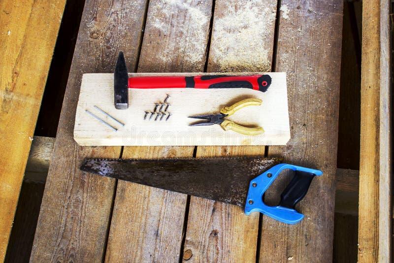 Verschiedene Handwerkzeuge: Metallsäge, Zangen, Schrauben, Hammer, Nägel - auf einer Stange und hölzerne unplaned Bretter Handwer stockbild