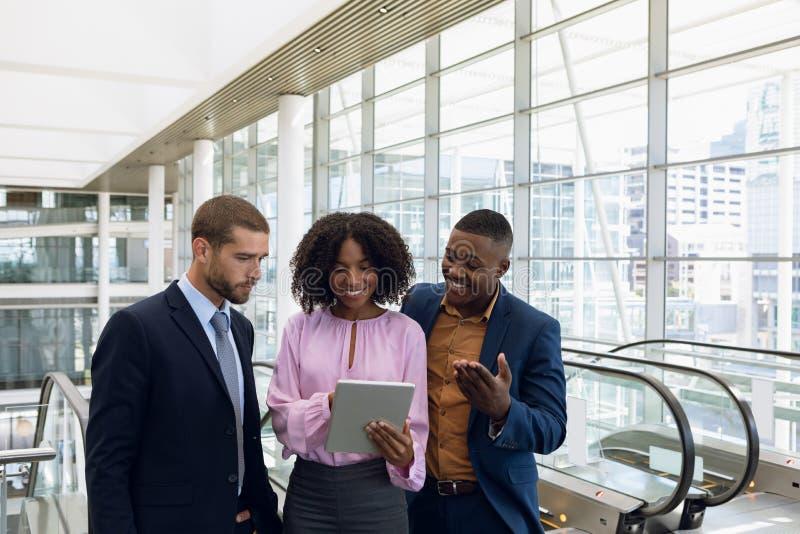 Verschiedene junge Geschäftsleute, die Tablette in der modernen Bürolobby verwenden stockbilder
