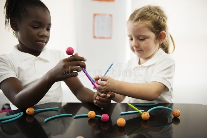 Verschiedene Kindergartenstudenten, die das Lernen von Strukturen von t halten stockfoto