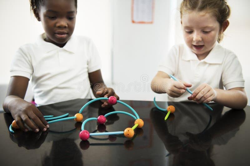 Verschiedene Kindergartenstudenten, die das Lernen von Strukturen von t halten stockbild