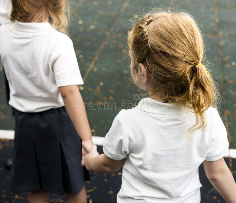 Verschiedene Kindergartenstudenten, die zusammen Händchenhalten stehen stockfoto