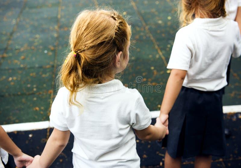Verschiedene Kindergartenstudenten, die zusammen Händchenhalten stehen stockbilder
