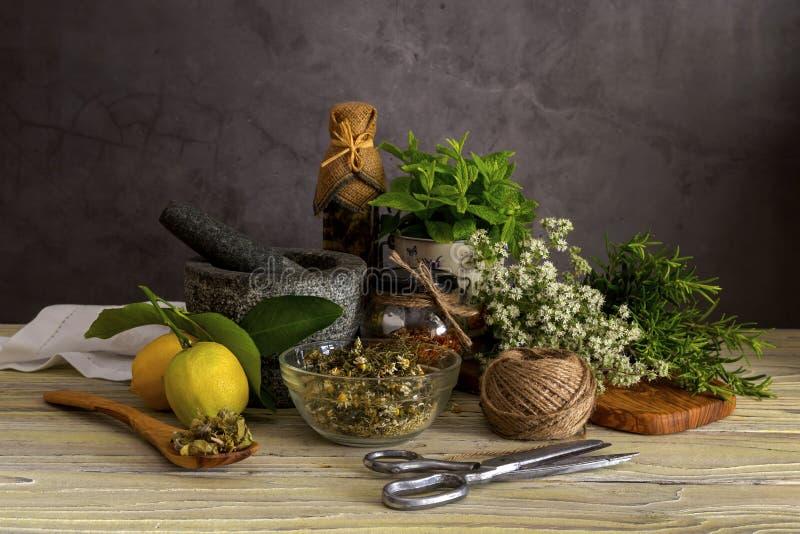 Verschiedene Kr?uter und Gew?rze, Zitronen und Oliven?l auf einem Holztisch stockfotos