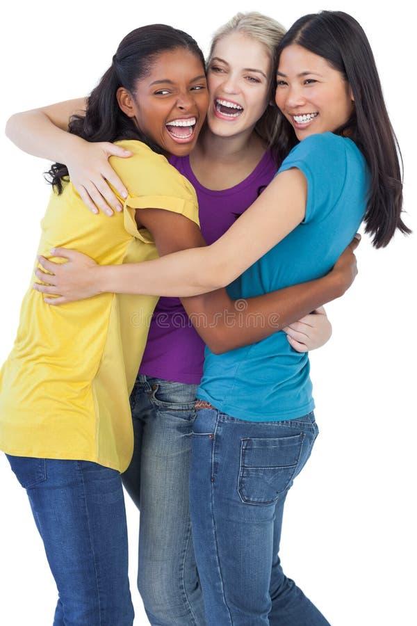 Verschiedene lachende Frauen, die sich umfassen stockfotografie