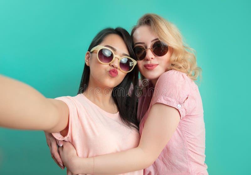 Verschiedene Mädchen in den zufälligen Ausstattungen, die das selfie lokalisiert auf blauem Hintergrund schießen stockfotos