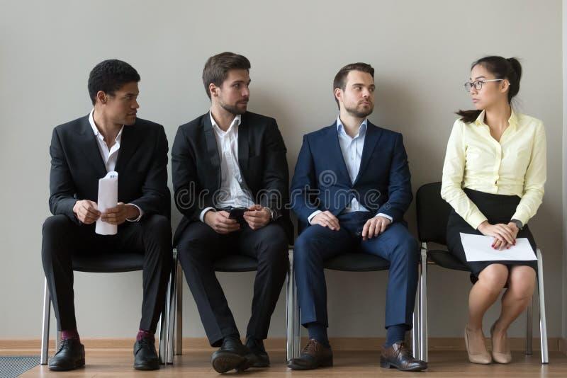 Verschiedene männliche Bewerber, die Warteinterview des weiblichen Rivalen betrachten stockfoto