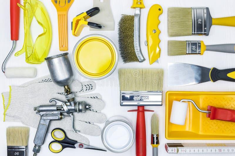 Verschiedene Malereiwerkzeuge für Hauserneuerung auf weißem hölzernem Schreibtisch lizenzfreie stockfotografie