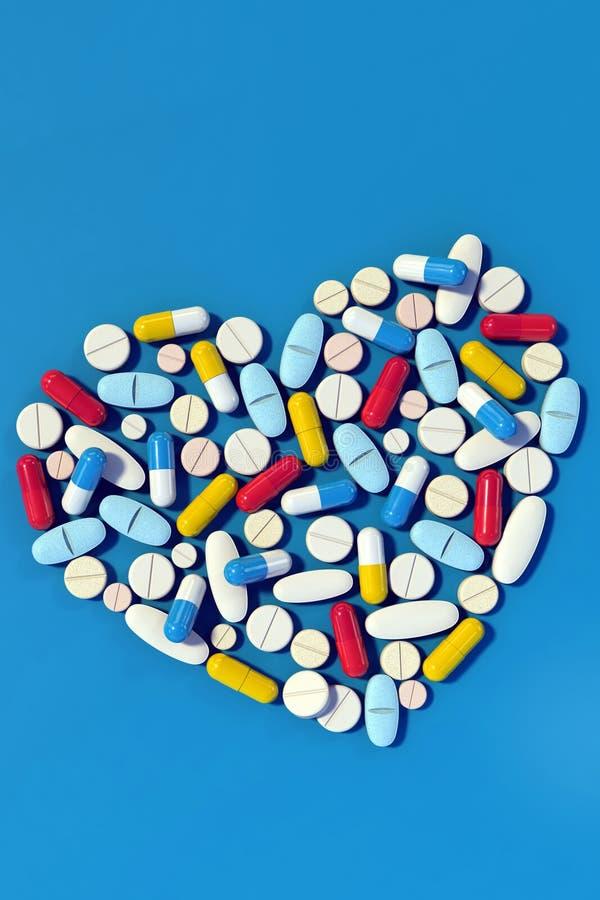 Verschiedene Medizinpillen vereinbarten in der Herzformvertikale stockfoto