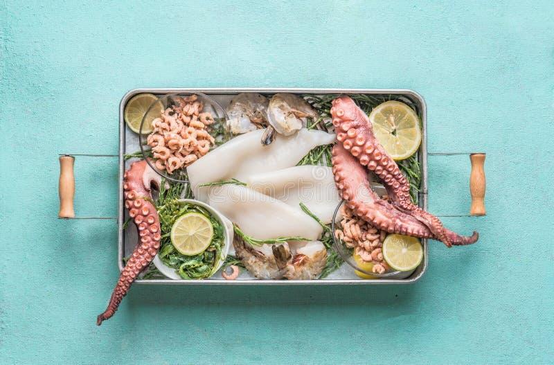 Verschiedene Meeresfrüchte im Behälter: Krake, Garnele, Kalmar und Meerespflanze auf hellblauem Hintergrund stockfoto