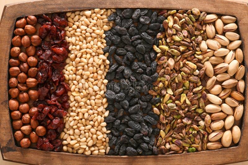 Verschiedene Nüsse und Trockenfrüchte auf hölzernem Behälter stockfoto