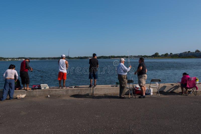 Verschiedene Sammlung Leute, die von einem Pier fischen lizenzfreie stockbilder