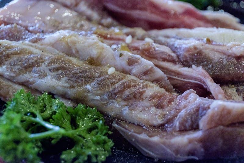 Verschiedene Schnitte des rohen Fleisches geschossen von oben auf einem Roheisengrill lizenzfreie stockfotos
