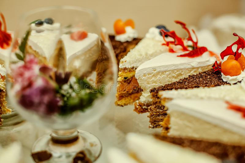 Verschiedene Stücke des sehr geschmackvollen Nachtischs des Kuchens mit nuts Beeren der Schokolade und unterschiedlicher Creme lizenzfreies stockfoto