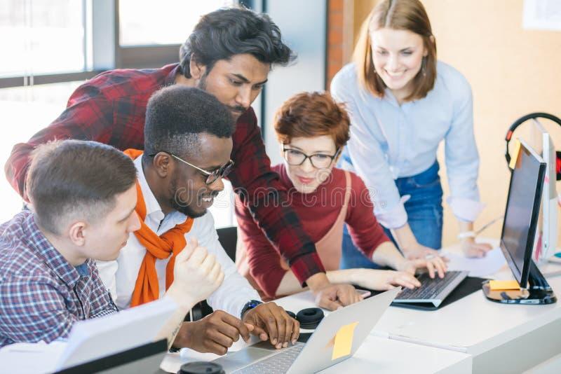 Verschiedene Studenten sitzen auf dem Netz zusammen schauen Sie interessanten Film lizenzfreies stockbild