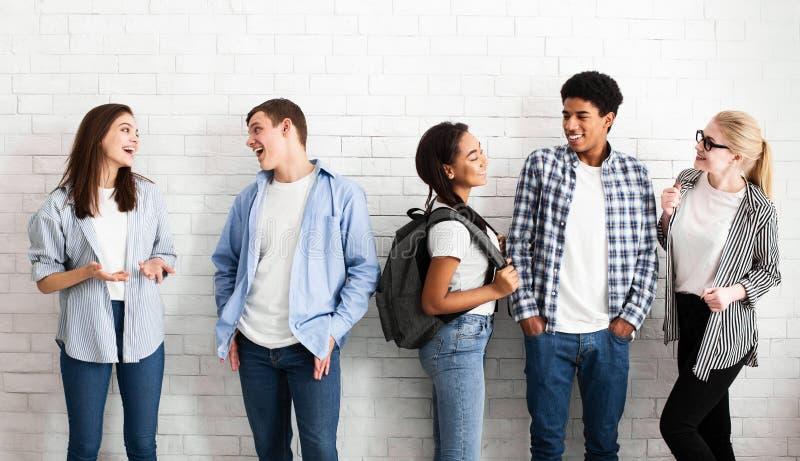 Verschiedene Studentenfreunde, die nahe Wand, Bruch habend sprechen stockfoto