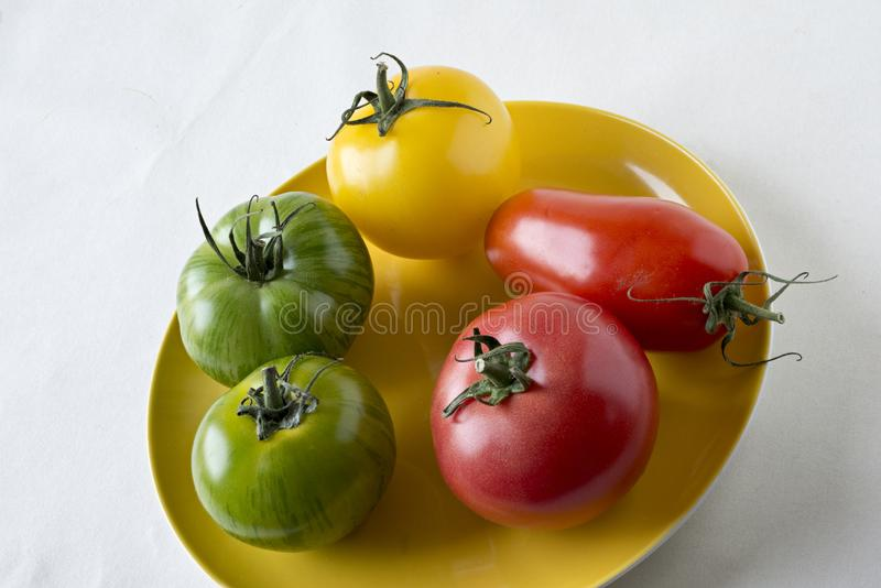 Yellow, red and green tomato varieties royalty free stock photography