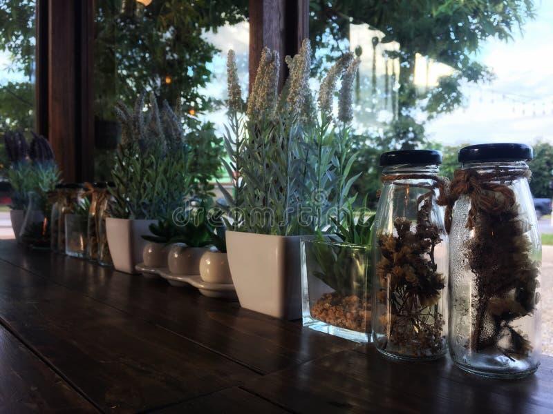 Verschiedene Trockenblumen in der nahen Flasche auf Holztisch stockfotografie