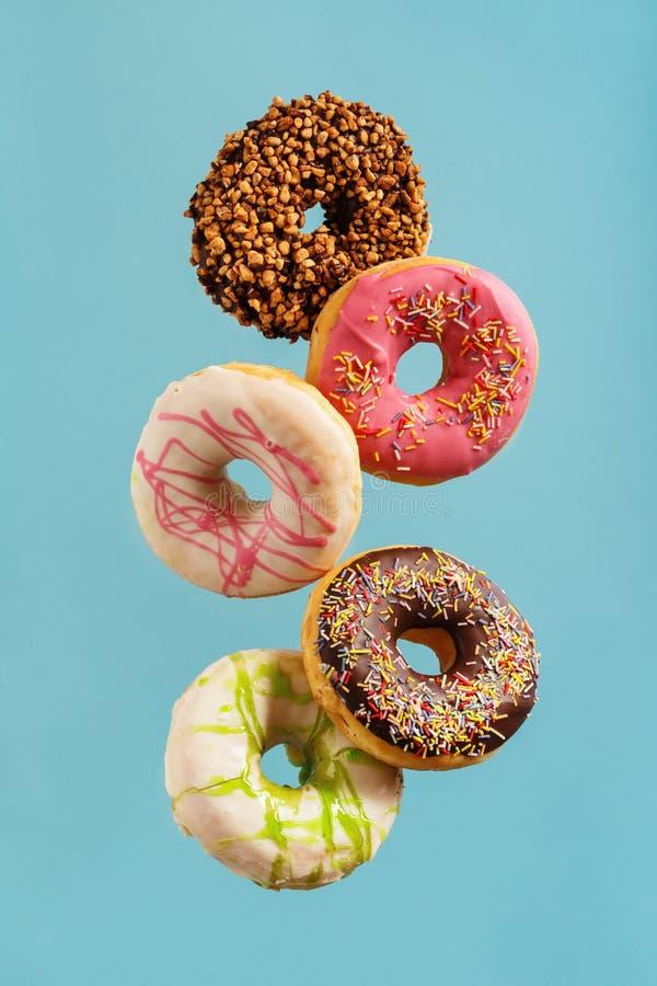 Verschiedene verzierte Donuts in der Bewegung, die auf blauen Hintergrund fällt stockfotos