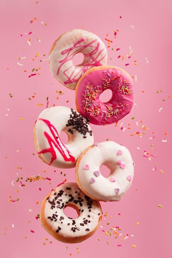 Verschiedene verzierte Donuts in der Bewegung, die auf rosa Hintergrund fällt stockbilder