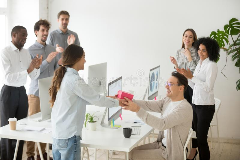 Verschiedener Kollege, der männlichen Mitarbeiter mit Geschenkbox beglückwünscht lizenzfreie stockfotos
