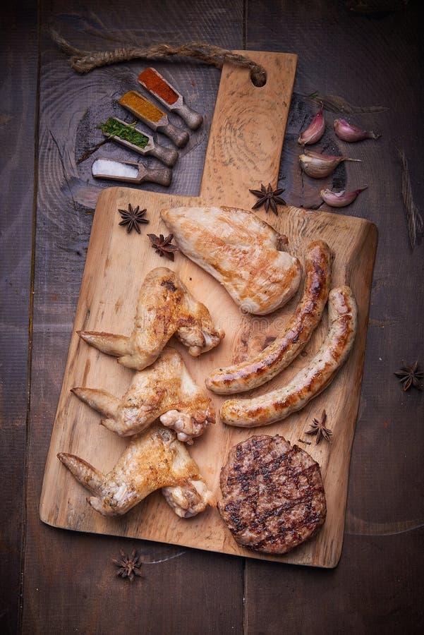 Verschiedenes Fleisch grillt, Lebensmittelhintergrund, hölzerner Hintergrund lizenzfreie stockfotos