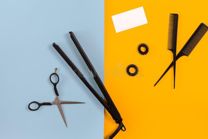Verschiedenes Haar, das Geräte auf der Farbe blau, gelber Papierhintergrund, Draufsicht anredet lizenzfreies stockbild