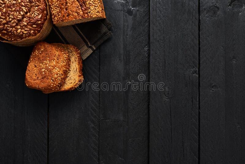 Verschiedenes krustiges Vollweizenbrot und Scheiben brot auf schwarzem wo lizenzfreies stockfoto