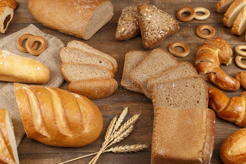 Verschillend brood op een donkere houten lijst stock afbeeldingen