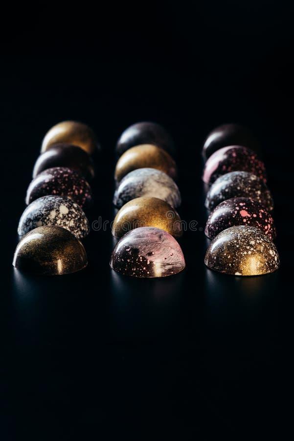 verschillend die chocoladesuikergoed in rijen wordt geplaatst stock afbeelding
